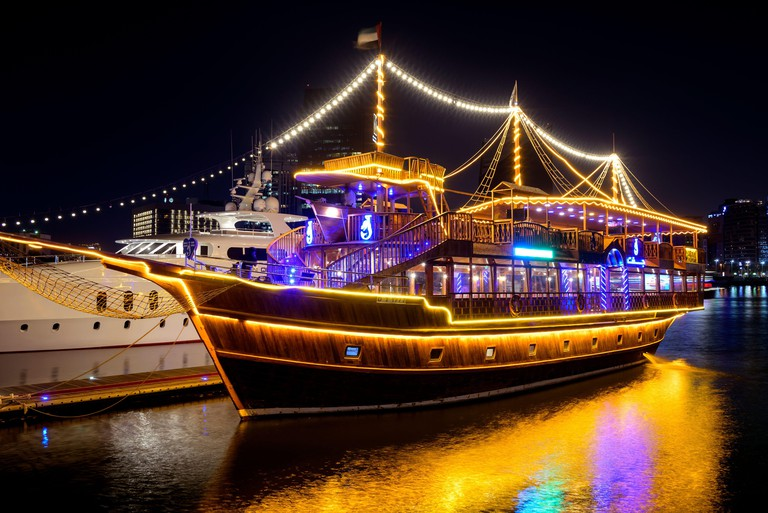 Beautifully illuminated Dhow cruise dinner ship showing reflections on water captured at the Al seef village , Dubai, UAE.