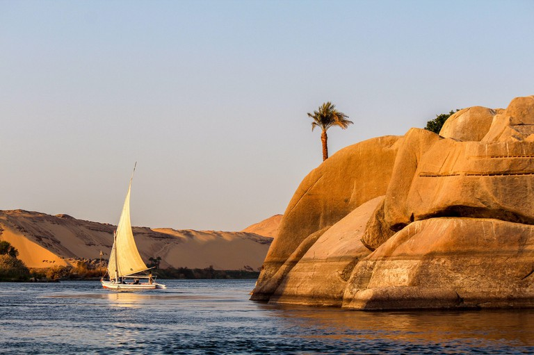 Sailboat on the Nile river at sunset, rock with ancient carvings in the front, Egypt