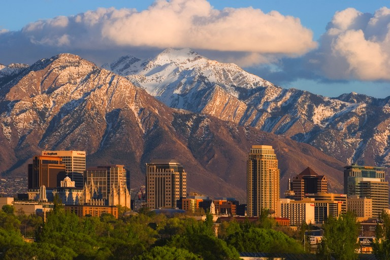 Salt Lake City Utah skyline showing downtown buildings and the snow-covered Wasatch Mountains in the background.