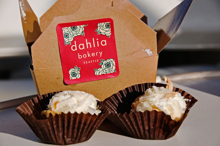 Two coconut cream pie bites are shown in front of bakery box from Dahlia Bakery in Seattle, Washington.