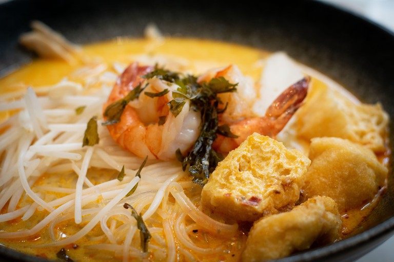 A bowl of laksa, typical soup from southeast asian which consists in wheat noodles, chicken, prawns and fish, served in spicy curry coconut milk