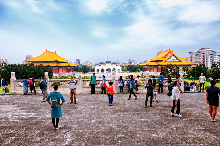 march 31, 2018.  Taipei, Taiwan. Tourists in front of the Chiang Kai-Shek Memorial with the national concert  and theater halls in the background in t