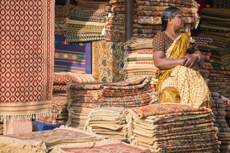 Woman selling carpets at Dili Haat in Delhi, India