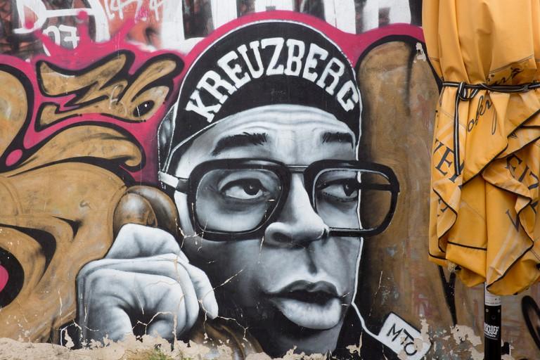 Street art graffiti on wall in Kreuzberg Hip hop style male character talking on phone with 'Kreuzberg' on cap Berlin Germany. Image shot 2013. Exact date unknown.