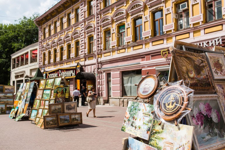 Tourists pass artworks for sale in Arbat street, Moscow, Russia