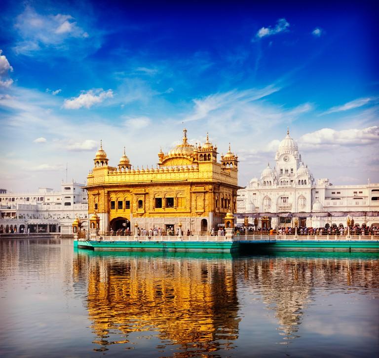 Vintage retro hipster style travel image of famous India attraction Sikh gurdwara Golden Temple (Harmandir Sahib). Amritsar,
