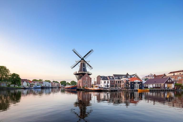 Landmark windmill De Adriaan in Haarlem Holland, The Netherlands. On the Spaarne River, canal with restaurant Zuidam