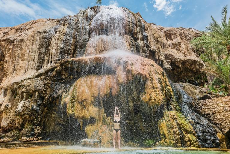 one woman bathing at ma'in hot springs waterfall in Jordan middle east