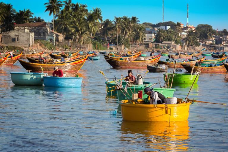 MUI NE, VIETNAM - FEBRUARY 08 - Fishermen in traditional small fishing boats