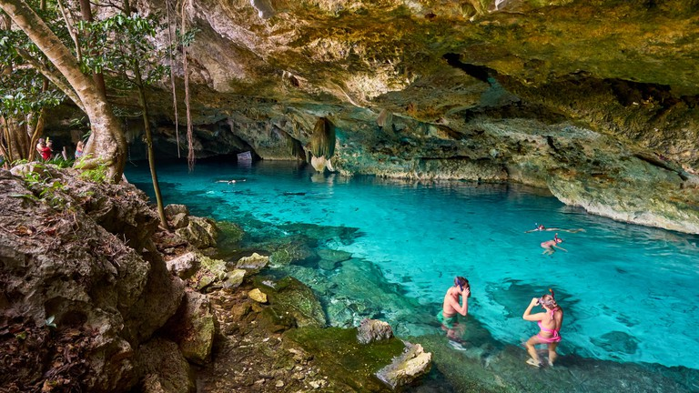 Tourist relaxing in Two Eyes Cenote (Cenote Dos Ojos), Yucatan, Mexico.