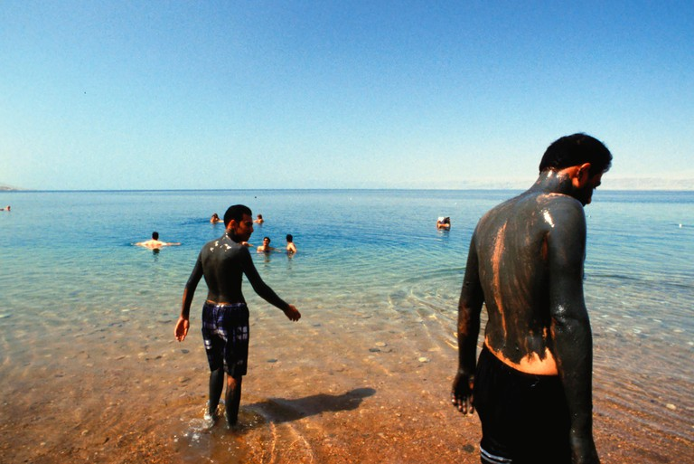 People covered with mud and swimming at the dead sea, Jordan