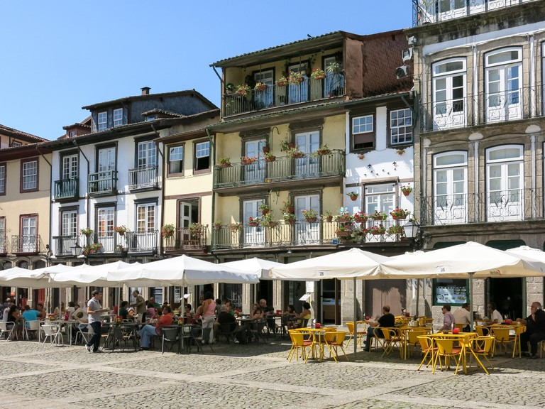People relaxing on pavement cafes on Oliveira Square in the historical centre of Guimaraes, Portugal