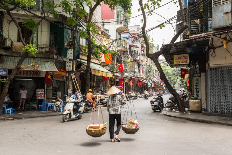 Street vendor transporting goods in baskets using a carrying pole in Hanoi's Old Quarter.