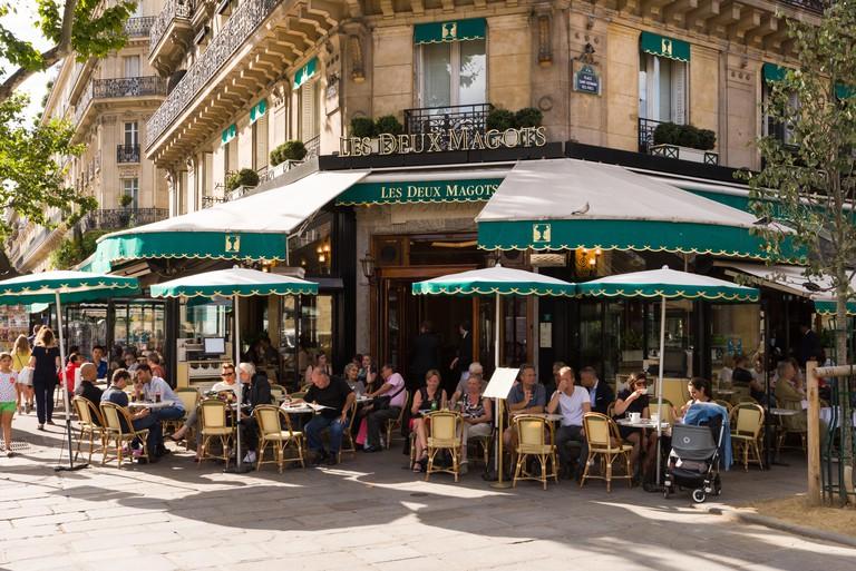 Patrons sit outside the Les Deux Magots cafe in Saint-Germain-des-Pres, Paris, France.
