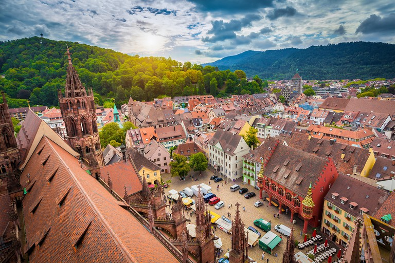 Aerial view of the historic city center of Freiburg im Breisgau from famous Freiburger Minster in beautiful evening light at sunset, Germany