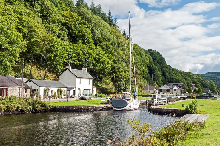 A Sailing vessel is approaching one of the locks on Crinan Canal at Cairnbaan in Argyll Scotland heading east towards Loch Fyne HHF9WC
