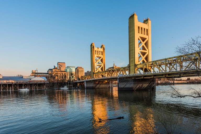 Gold Tower Bridge, in Sacramento California during blue sunset with downtown and goose