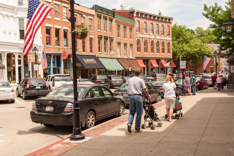 Man and woman pushing their children in strollers down Main Street, Galena, Illinois, USA