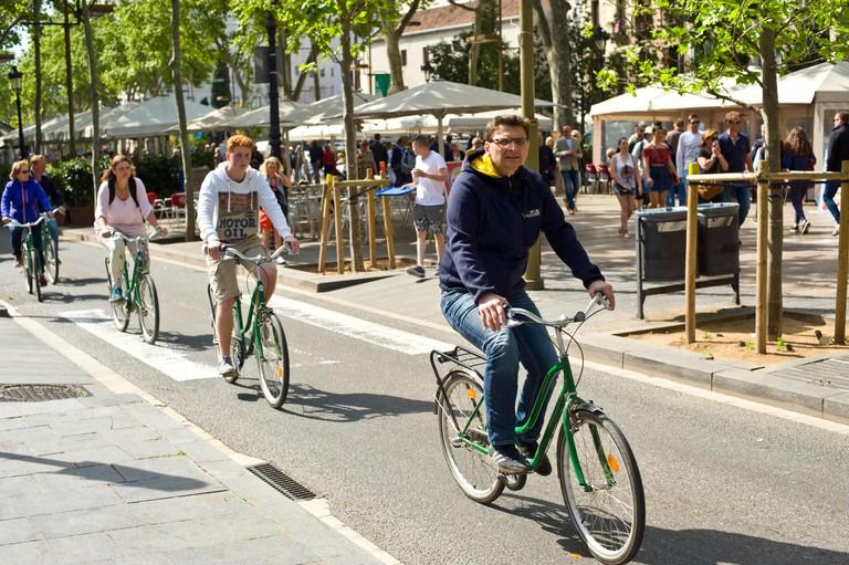 Bicycle tourists on La Rambla in Barcelona Spain ES EU