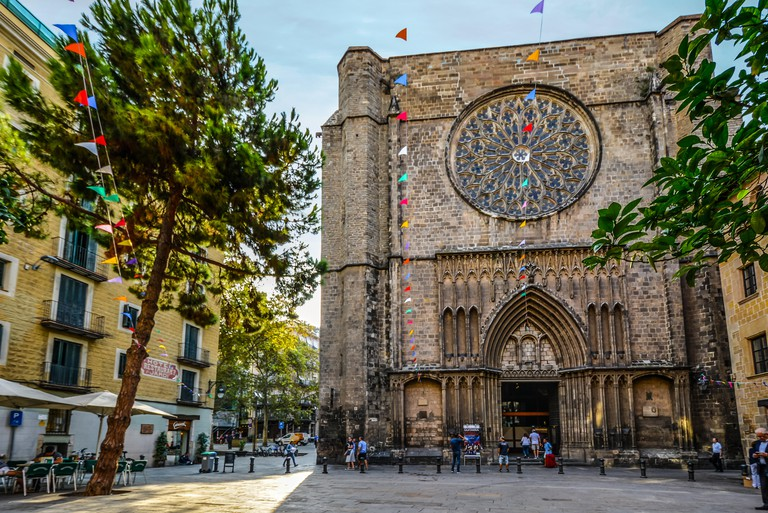 14th-century Gothic church Santa Maria del Pi in the gothic quarter of Barcelona Spain in Placa del Pi with colorful flags and a small cafe