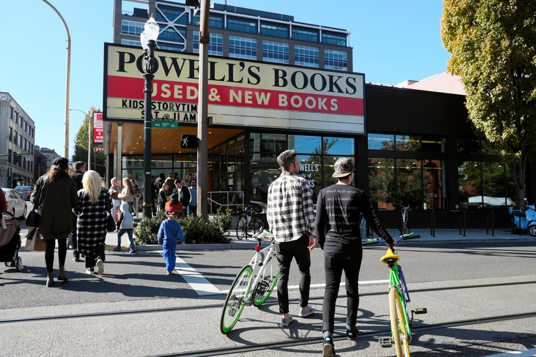 Exterior view of men with bikes crossing road outside Powell's Books famous book store in Portland Oregon USA  KATHY DEWITT