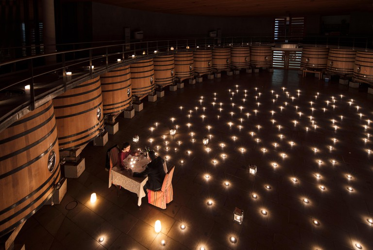 Couple having a romantic dinner in the fermentation room of Clos Apalta winery. Colchagua Valley, Chile.