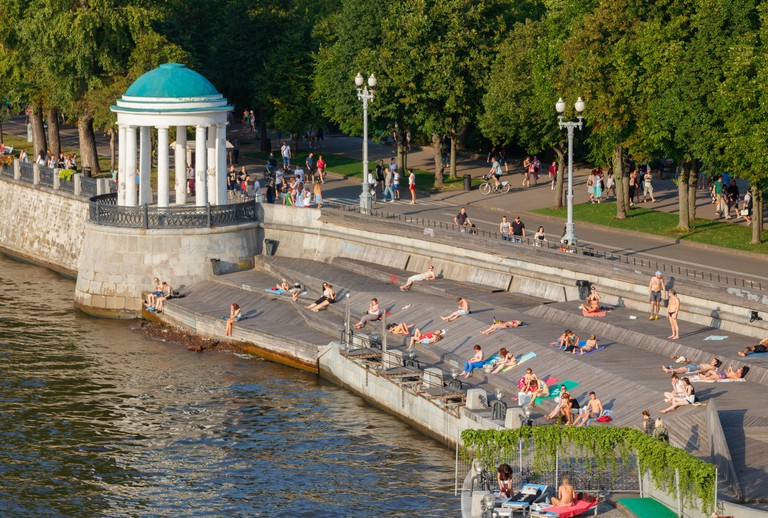 Unidentified people sunbathing at the Gorky Park at Moskva River bank on a sunny day. Moscow, Russia.