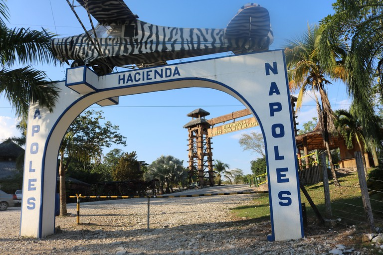The entrance gate reads 'Hacienda Napoles', Colombia, 07 December 2017. The Hacienda once belonged to drug lord Pablo Escobar who set up a private zoo here. Today, the Hacienda is a amusement park. The airplane above the entrance was the first airplane Es