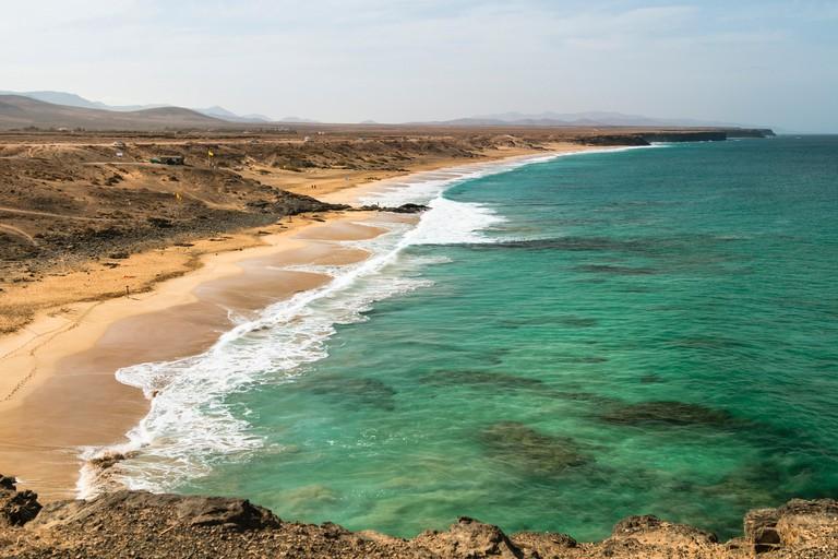 Turquoise water at the beach Playa del Aljibe de la Cueva near El Cotillo in Fuerteventura, Spain with tall waves.