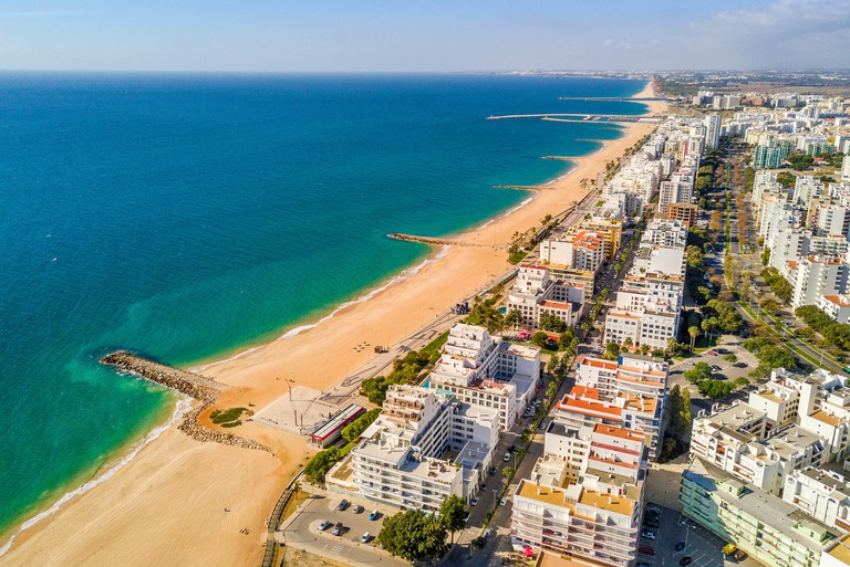 Aerial view, wide sandy beach in touristic resorts of Quarteira and Vilamoura, Algarve, Portugal