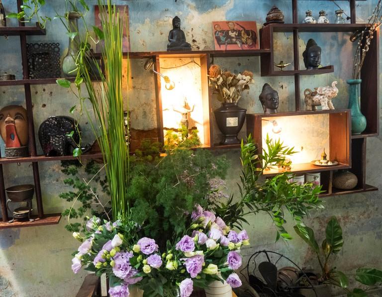 Buddha ornaments and a bouquet of flowers Padma de Fleur, a florist shop and restaurant, in Ho Chi Minh City, Vietnam.