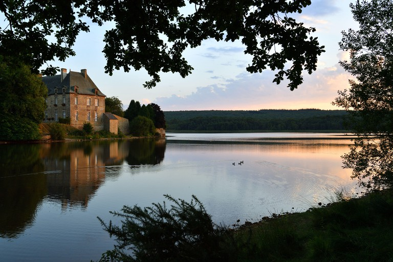 France, Morbihan, Broceliande Forest, Paimpont, the abbey of 13th century in edge of the pond, sunset