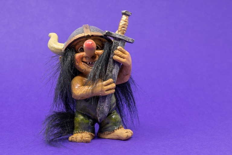 A toy, ornamental troll with a huge nose and big eyes wearing a viking helmet holding a large, oversized sword.