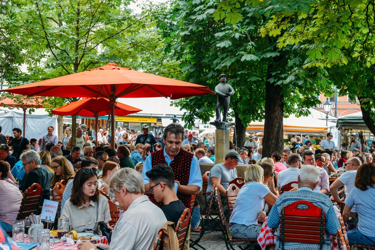 Munich, Germany - July 29, 2018: Locals and tourists enjoy beer and food at an open air beer garden in Viktualienmarkt in the historic centre of Munic