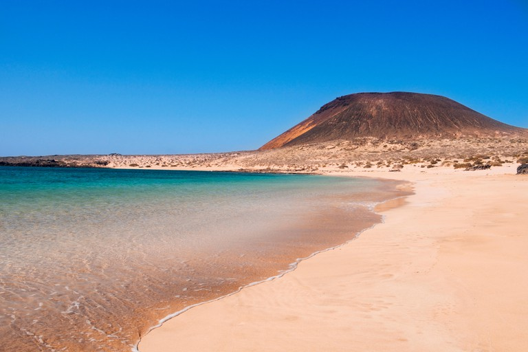 a view of La Francesa Beach in La Graciosa island, in the Canary Islands, Spain, with the Montana Amarilla mountain in the background