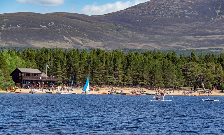 Loch Morlich and Cairngorms in Glenmore Cairngorms National Park Highland Scotland with the east beach full of visitors and boats