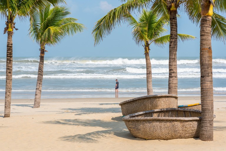 My Khe beach with a figure of a young traveler, traditional Vietnamese coracles (round wicker boats) lying on the sand, palm trees and coming waves.