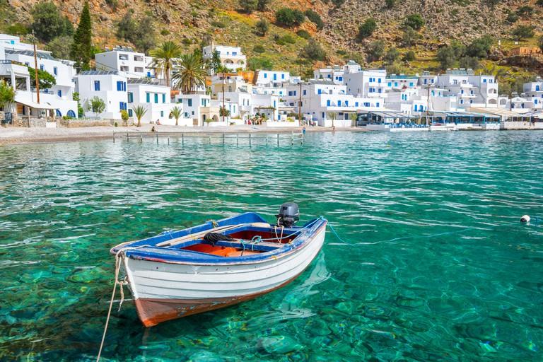 Fishing boat and the scenic village of Loutro in Crete, Greece