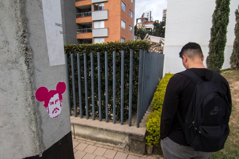 22 February 2019, Colombia, Medellin: A young man stands next to a graffiti with a picture of Pablo Escobar, while in the background the ruins of the recently blown up Monaco building can be seen. The building was the drug baron's house. Photo: Daniel Rom