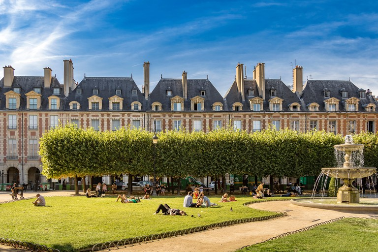 People sitting and sunbathing near the The fountain on a hot summer's day at Place des Vosges ,in the fashionable Le Marais district of Paris .