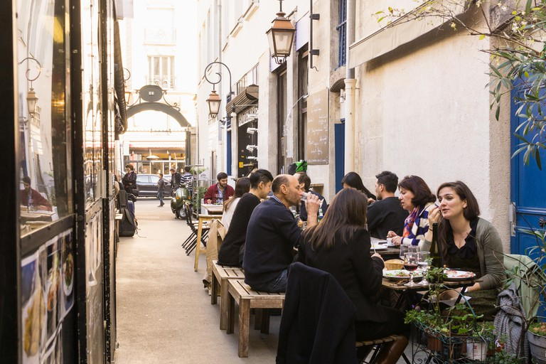 Paris food market - People having lunch break in eateries at the Marche des Enfants Rouges in the Marais district of Paris, France.