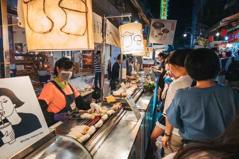 A woman grills king oyster mushrooms for a queue of customers at a food stall in Shi Lin Night Market, Taipei, Taiwan