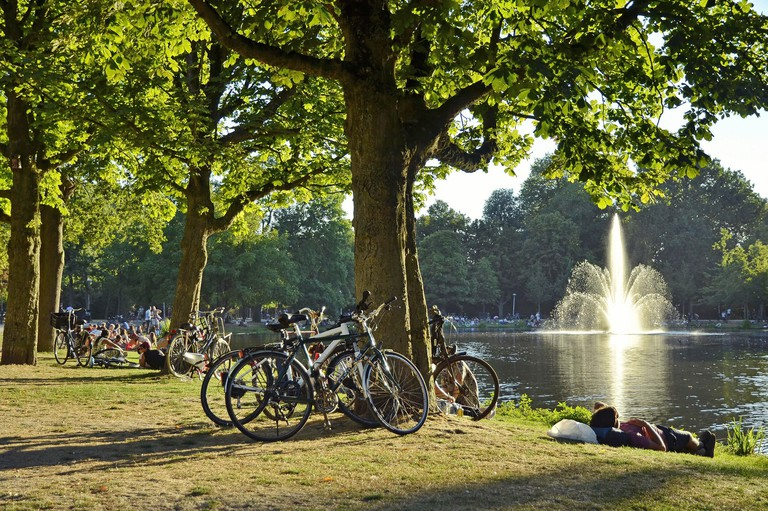 View of the fontain in the Vondelpark among the relaxing crowd and parking bicycles, under the late summer sun