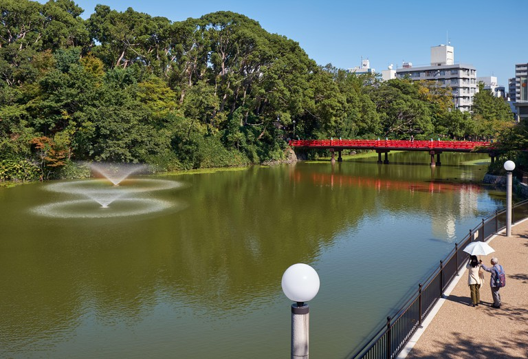 2APFC6D OSAKA, JAPAN - OCTOBER 16, 2019: The view of Kawazokoike Pond with fountains and the red bridge in Tennoji Park of Osaka. Japan