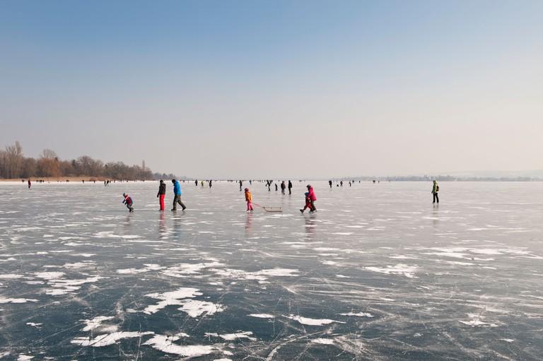People walking on the ice of a frozen Lake Constance, Markelfinger Winkel, Radolfzell, Konstanz district, Baden-Wuerttemberg - CRAJ9B