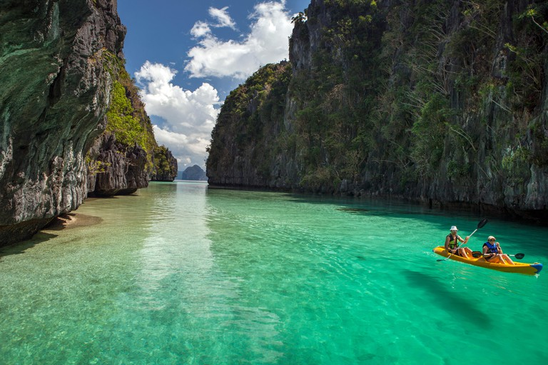 PHILIPPINES, Palawan, El Nido, Miniloc Island, tourists kayak through the crystal clear waters of Big Lagoon on Miniloc Island located in Bacuit Bay i