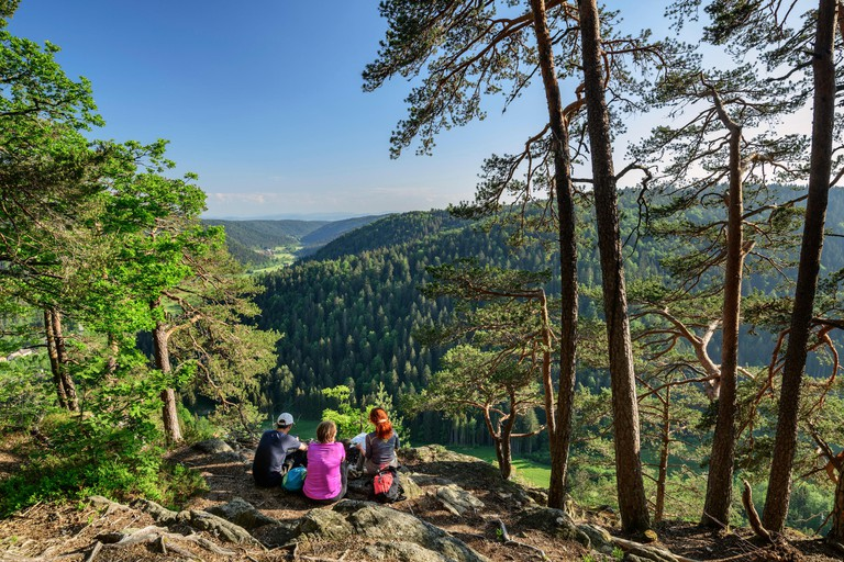 Three persons sitting at vista-point and looking towards valley of Alb, Dachsberg, Albsteig, Black Forest, Baden-Wuerttemberg, Germany