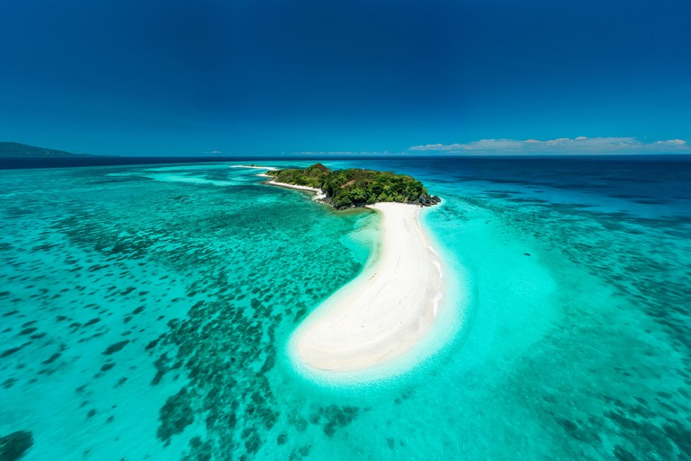 Truly amazing tropical island in the middle of the ocean. Aerial view of an island with white sand beaches and beautiful lagoons