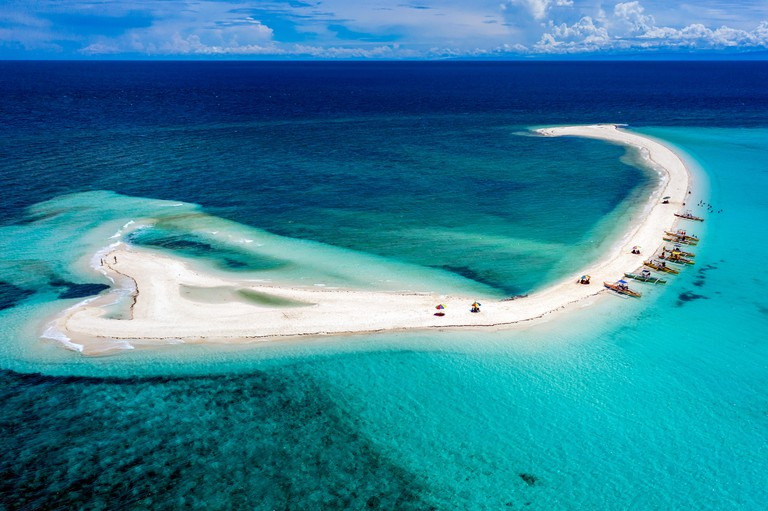 Aerial drone view of a spectacular sandbar surrounded by coral reef located off a tropical island (White Island, Camiguin, Philippines)