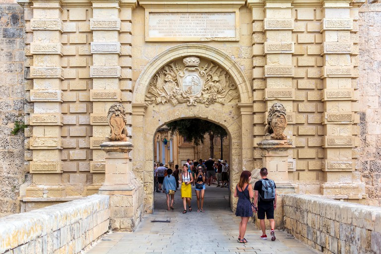 Tourists walking through Baroque portal of Mdina Gate, also known as the Main Gate or the Vilhena Gate